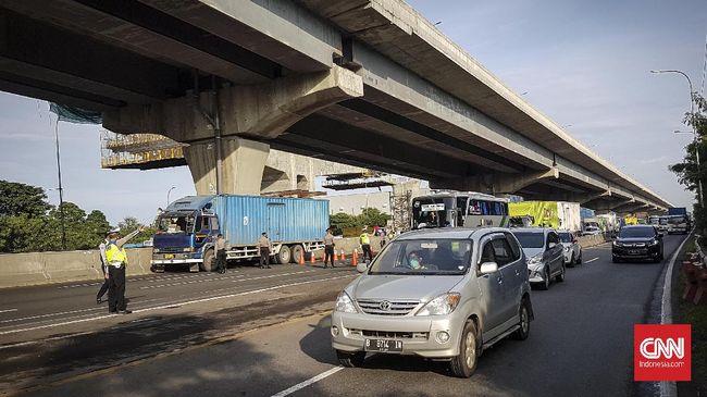 Petugas kepolisian mengecek kendaraan yang melintas di Jalan Tol dari arah Jakarta menuju Cikampek, Jumat (24/6) di Posko Check Point di Gerbang Cikarang Barat, Bekasi, Jawa Barat. Para pengemudi kendaraan yang tidak berkepentingan atau ketahuan hendak mudik diarahkan langsung untun masuk ke Gerbang Tol Cikarang Barat untuk memutat balik kembali ke Jakarta
