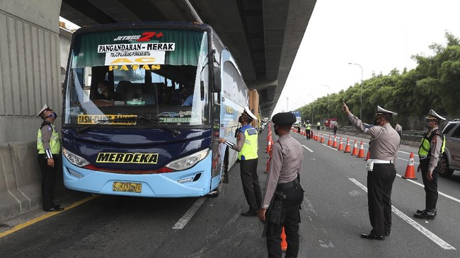 Indonesian police check bus passengers at a checkpoint during the imposition of large-scale restriction to curb the spread of the new coronavirus outbreak on toll road in Cikarang, West Java, Indonesia, Friday, April 24, 2020. Indonesia is suspending passenger flights and rail service as it restricts people in the world's most populous Muslim nation from traveling to their hometowns during the Islamic holy month of Ramadan because of the coronavirus outbreak. (AP Photo/Achmad Ibrahim)