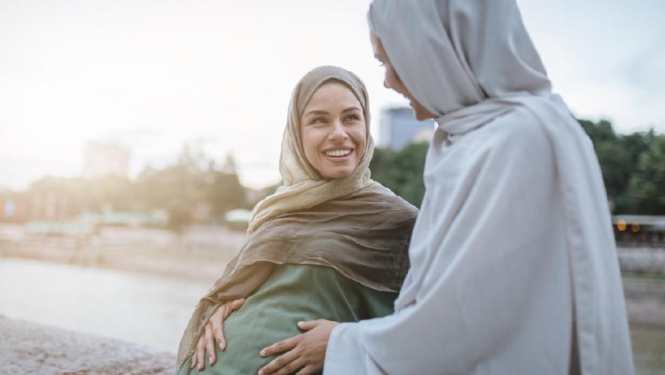 Cute and lovely pregnant Muslim woman and her Muslim friend, spending the time together on a city street.