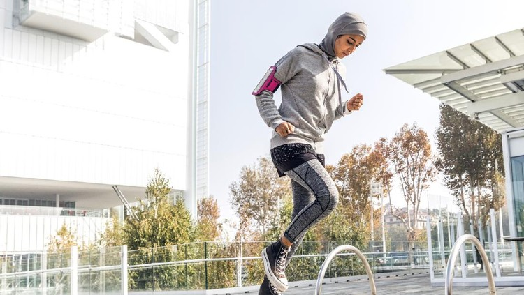 Athletic muslim woman is exercising on staircase