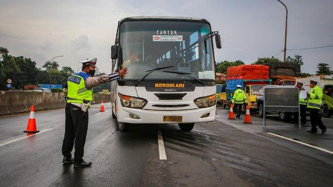Petugas kepolisian mengarahkan bus ke pintu keluar Tol Bitung, Kabupaten Tangerang, Banten, Jumat (24/4/2020). Penyekatan itu dilakukan menyusul adanya larangan mudik bagi seluruh kalangan yang sudah ditetapkan mulai hari ini guna mencegah penyebaran COVID-19. ANTARA FOTO/Fauzan/wsj.