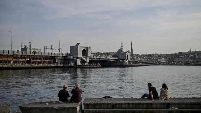 People sit on the shore side of Bosphorus strait' Golden Horn, in front of Galata bridge on April 14, 2020 in Istanbul a day after Turkish President ordered a fresh lockdown next weekend, warning the move would be imposed as long as necessary to stop the spread of the COVID-19 disease caused by the novel coronavirus. (Photo by Ozan KOSE / AFP)