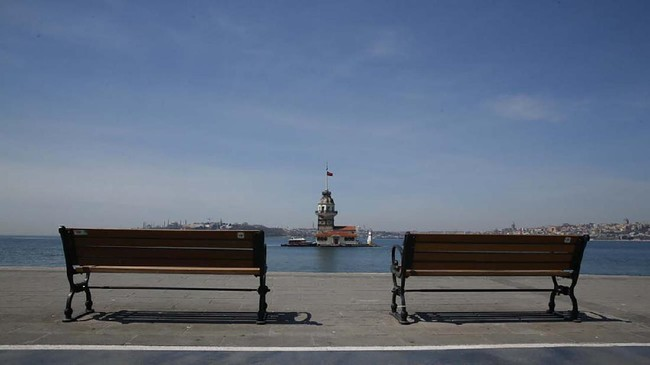 Istanbul's iconic Maiden's Tower (Kiz Kulesi) flanked by empty benches by the Bosphorus Strait separating the European and Asian sides of Istanbul, Sunday, April 19, 2020, on the second day of the two-day curfew declared by Turkey's government in an attempt to control the spread of coronavirus. (AP Photo/Mehmet Guzel)