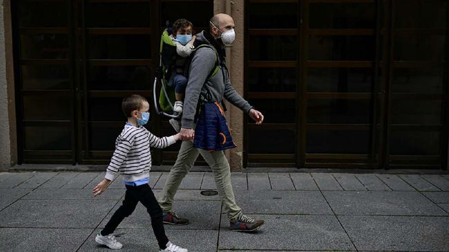 A father with his children wearing face mask to prevent the coronavirus go for a walk at Carlos III promenade, in Pamplona, northern Spain, Sunday, April 27, 2020. On Sunday, children under 14 years old will be allowed to take walks with a parent for up to one hour and within one kilometer from home, ending six weeks of compete seclusion. (AP Photo/Alvaro Barrientos)