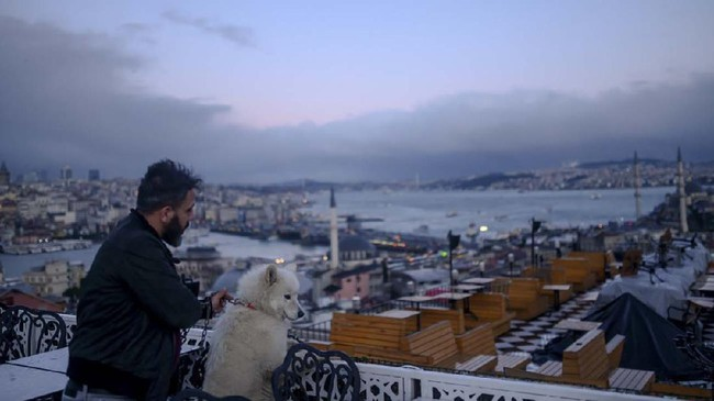 A man with his dog looks at the Bosphorus view from a terrace at Eminonu, in Istanbul, on January 2, 2020. (Photo by BULENT KILIC / AFP)
