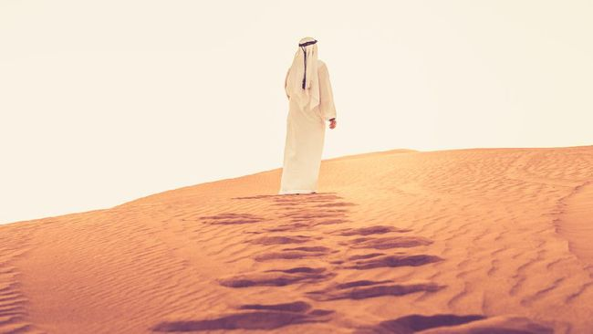 Arab walking on the sand dunes of Dubai and looking at the bright sunlight.