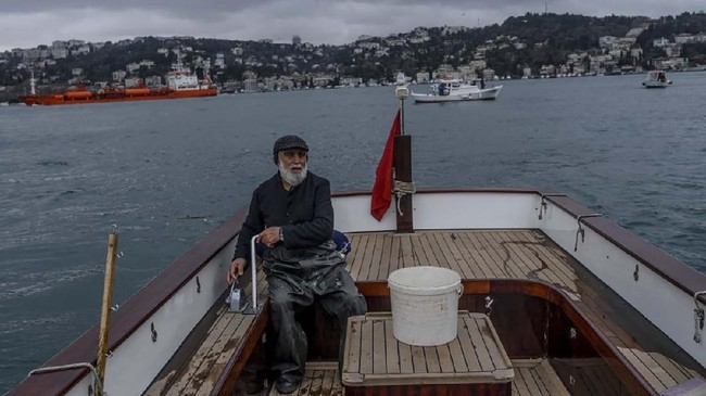 Bosphorus fisherman Irfan, manuevers his fishing boat along the Bosphorus Strait on January 16, 2020, in Istanbul. - Irfan is a retired sea captain whose father was also a fisherman on the Bosphorus. (Photo by BULENT KILIC / AFP)
