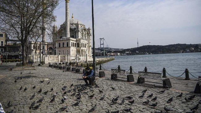 A Turkish police feeds pigeons as July 15 Martyrs' Bridge, known as the Bosphorus Bridge and Ortakoy mosque are seen in the backround in Istanbul on April 11, 2020, as Turkish government announced a two-day curfew to prevent the spread of the epidemic COVID-19 caused by the novel coronavirus. (Photo by Ozan KOSE / AFP)