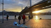 People stand next to Bosphorus strait's Golden horn at sunset while the metro bridge is seen in the background at Karakoy district in Istanbul on January 18, 2020. (Photo by Yasin AKGUL / AFP)