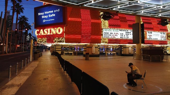 In this April 19, 2020, photo, a lone security guard watches over casinos shuttered due to the coronavirus outbreak in Las Vegas.