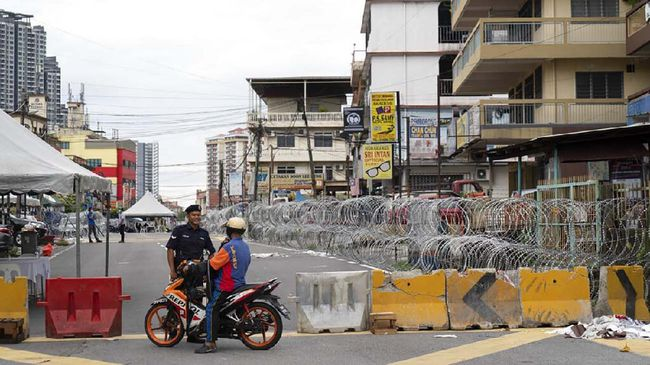 Malaysian Police check a motorcyclist next to barbed wire in the locked down area of Selayang Baru, on the outskirt of Kuala Lumpur, Malaysia, on Sunday, April 26, 2020. The lockdown was implemented to allow authorities to carry out COVID-19 screenings to curb the spread of coronavirus. (AP Photo/Vincent Thian)