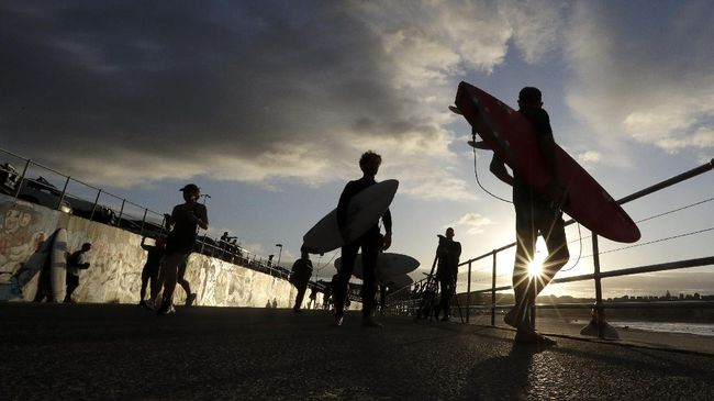 A sign indicates the beach is closed as a surfers arrives for the 7A.M. opening of Bondi Beach in Sydney, Tuesday, April 28, 2020, as coronavirus pandemic restrictions are eased. The beach is open to swimmers and surfers to exercise only. (AP Photo/Rick Rycroft)
