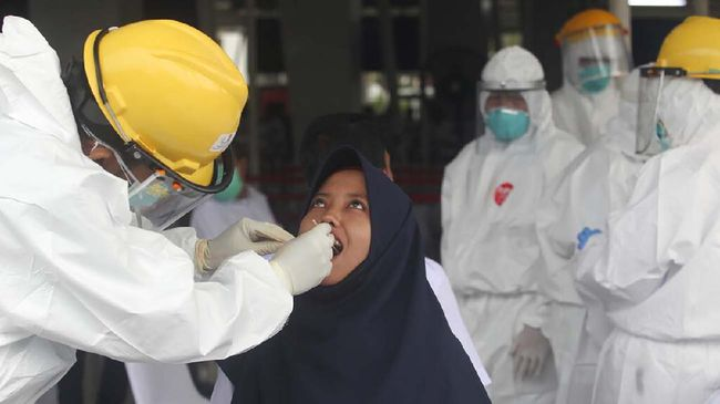 A health worker conducts a swab test for the new coronavirus on a Muslim woman, in Bogor, Indonesia, Monday, April 27, 2020. The world's Muslims have begun Ramadan with dawn-to-dusk fasting amid restrictions imposed to slow the pandemic that left many confined to their homes and public venues like parks, malls and even mosques are shuttered. (AP Photo/Arr Rayan)