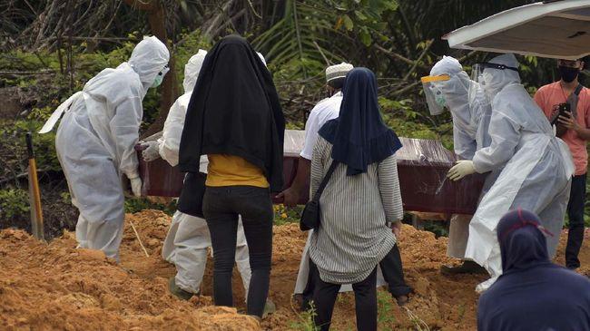 Sejumlah keluarga pasien memperhatikan tenaga medis dan penggali kubur yang mengenakan alat pelindung diri saat proses pemakaman keluarganya di Tempat Pemakaman Umum (TPU) Tengku Mahmud Palas di Kota Pekanbaru, Riau, Selasa (28/4/2020). Pemerintah Indonesia menyatakan hingga 28 April pukul 12.00 WIB, jumlah kematian akibat COVID-19 mencapai 773 orang dari 9.511 kasus terkonfirmasi positif, sedangkan yang sembuh ada 1.254 orang. ANTARA FOTO/FB Anggoro/hp.