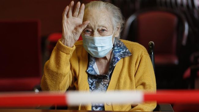 Marguerite Mouille, 94, waves goodbye to her visiting daughter at the Kaisesberg nursing home, eastern France, Tuesday April 21, 2020. France banned all nursing home visits early in the pandemic, and many residents have been confined to their rooms for weeks, because the coronavirus has been especially dangerous for the elderly. France made an exception to its strict virus confinement measures to allow families to visit relatives in nursing homes since Monday. (AP Photo/Jean-Francois Badias)