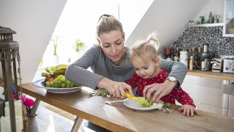 A mother and child sat in a kitchen eating fruit together.