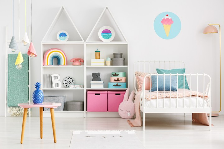 Front view of a kid's room with a table, shelves with boxes and rainbow, single bed and ice cream poster on the wall