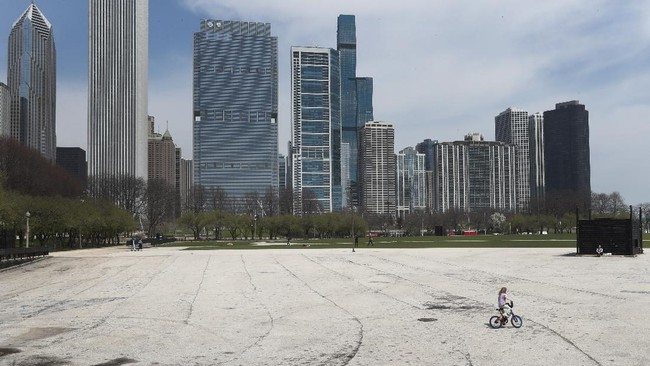 Ella Frank, of Chicago, rides her bike as he mother Gozde watches at the Petrillo Music Pavilion, the site of many summertime live music events, in Chicago's Grant Park Tuesday, April 28, 2020. From Cape Cod to California, festivals are being nixed, businesses in tourist havens are looking at empty reservation books, and people who have been cooped up through a dismal spring are worrying summer will bring just more of the same. (AP Photo/Charles Rex Arbogast)