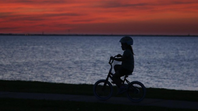 In this April 27, 2020, photo, a girl rides her bicycle as the sun sets at Lake Hefner in Oklahoma City. From Cape Cod to California, festivals are being canceled, businesses in tourist havens are looking at empty reservation books, and people who have been cooped up through a dismal spring are worrying summer will bring just more of the same. (AP Photo/Sue Ogrocki)