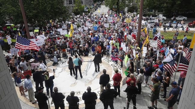 People gather outside the North Carolina Legislative Building to protest the current stay-at-home orders issued by Gov. Roy Cooper amid the outbreak of COVID-19 in Raleigh, N.C., Tuesday, April 28, 2020. (AP Photo/Gerry Broome)
