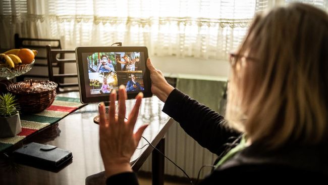 Older woman talking via video call. Sit at home on the recommendation of a doctor. An older woman uses tablet
