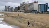 FILE - In this April 4, 2020, file photo, windy and cool conditions did not attract many visitors to the beach in Virginia Beach, Va. Along Virginia's coast, a long list of festivals have already been canceled, and the usually bustling Virginia Beach oceanfront sits quiet and empty. (AP Photo/Steve Helber, File)