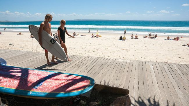 Noosa, Queensland, Australia - March 11, 2014:  Young couple carrying a surfboard and talking walk along the walkway by the beach where sunbathers are out in the sun at this Sunshine Coast holiday beach destination of Noosa.