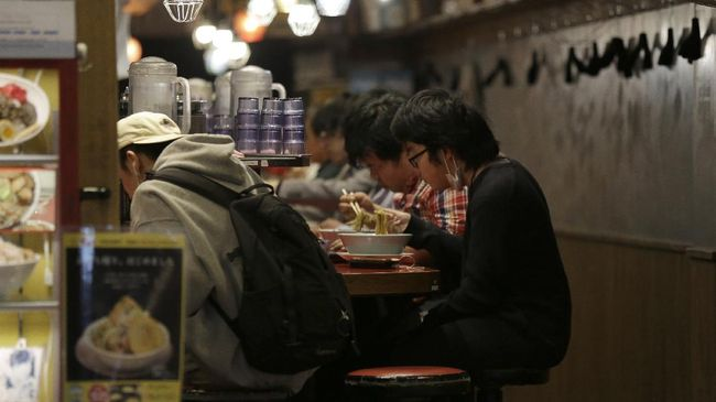 In this April 25, 2020, photo, people eat at a small ramen shop in the entertainment district near Shibuya station right before the 8pm government requested closing time for restaurants and bars in Tokyo. Under Japan's coronavirus state of emergency, people have been asked to stay home. Many are not. Some still have to commute to their jobs despite risks of infection, while others are dining out, picnicking in parks and crowding into grocery stores with scant regard for social distancing. (AP Photo/Kiichiro Sato)