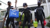 Dolphin trainers wear face masks as they carry containers to feed dolphins at a conservation center in Bali, Indonesia on Tuesday, April 28, 2020 during a temporal closure to public due to the concerns over a new coronavirus infection. All tourist attractions and sites have been asked to temporarily close as a measure to control the spread of the virus outbreak. (AP Photo/Firdia Lisnawati)