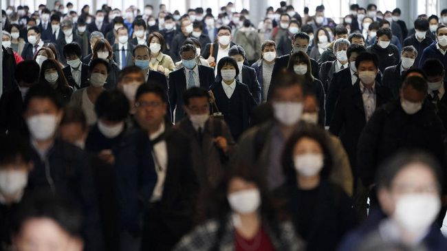 FILE - In this April 27, 2020, file photo, a station passageway is crowded with commuters wearing face mask in Tokyo. Under Japan's coronavirus state of emergency, people have been asked to stay home. Many are not. Some still have to commute to their jobs despite risks of infection, while others are dining out, picnicking in parks and crowding into grocery stores with scant regard for social distancing. (AP Photo/Eugene Hoshiko, File)
