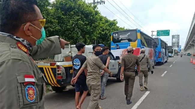 Petugas Gugus Tugas Penanganan Covid-19 Palembang melakukan patroli dalam hari pertama penerapan kebijakan wajib mengenakan masker di Palembang, Kamis (30/4). Dari patroli yang dilakukan hingga siang hari, 33 orang dibawa ke pusat karantina karena tidak bermasker.