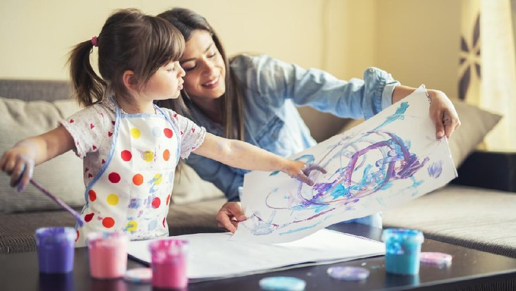 A young mother and her cute little daughter painting with colorful paints and having fun at home.