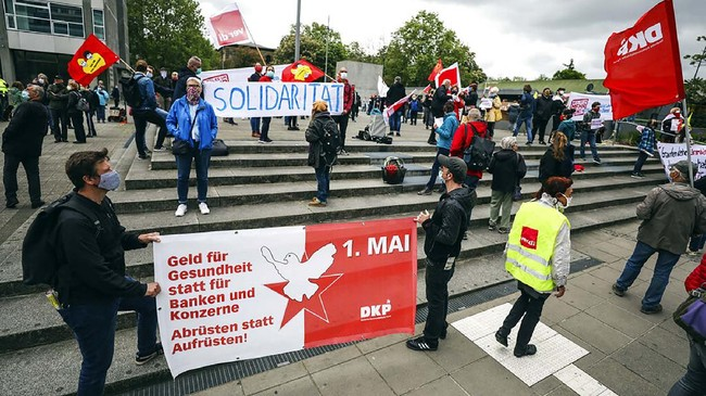 People take part in a rally for better health care and more solidarity in Stuttgart, Germany, Friday May 1, 2020. May Day will be different in 2020, as the coronavirus lockdown measures in effect across the globe will curtail the usual protests and gatherings. (Christoph Schmidt/dpa via AP)