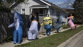 The T-Rex Walking Club, a group of people that gather in a variety of inflatable costumes parade through neighborhoods in hopes of cheering up the community during the COVID-19, coronavirus in Ferndale, Michigan, on April 27, 2020. (Photo by Emily Elconin / AFP)