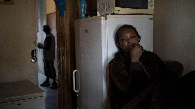 A woman sits inside her room in downtown Johannesburg, South Africa on April 14, 2020. A total of 23 families of blind and disabled foreign nationals living in the dilapidated building and earning a living by street begging have been hard hit by South Africa's lockdown as they are forced to remain indoors. (AP Photo/Bram Janssen)