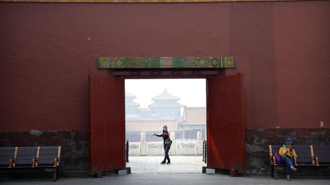 A visitor wearing a face mask to protect against the new coronavirus walks through the Forbidden City in Beijing, Friday, May 1, 2020. The Forbidden City reopened beginning on Friday, China's May Day holiday, to limited visitors after being closed to the public for more than three months during the coronavirus outbreak. (AP Photo/Mark Schiefelbein)