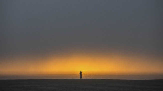 A woman watches the sunset from the beach in Venice, California on April 26, 2020. - Los Angeles County beaches are still off limits under Los Angeles countyís
