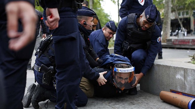 A man is arrested by police officers during a May Day demonstration, in Paris, during nationwide confinement measures to counter the Covid-19, Friday, May 1, 2020. France is bracing for potential wildcat demonstrations despite a ban on any gatherings. Unions are calling for people to sing on balconies or out their windows at midday in a collective shout of protest for more worker protections. (AP Photo/Thibault Camus)