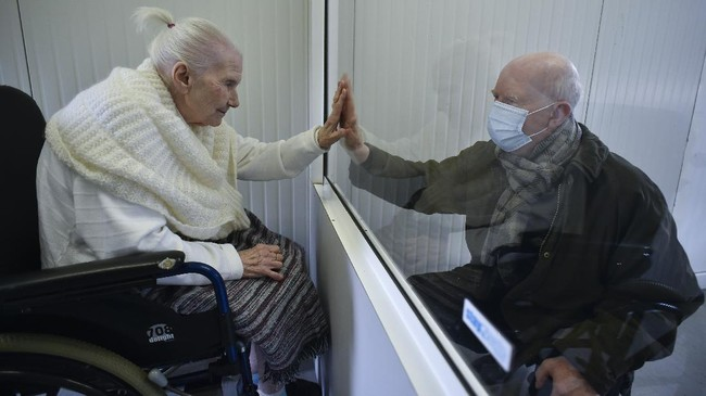 Suzanne Valette, 88,infected with COVID-19, meets with her son Philippe Melard through a plexiglass lock inside the contenair at the Buissonets retirement home which has been converted into a visiting room for the relatives, in Horion-Hozemont a section of the municipality of Grace-Hollogne, on April 29, 2020. - Belgium is in its seventh week of confinement in the ongoing corona virus crisis. The government has announced a phased plan to attempt an exit from the lockdown situation in the country, continuing to avoid the spread of Covid-19. (Photo by JOHN THYS / AFP)