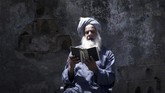 A Palestinian man reads the Koran during the holy month of Ramadan in Gaza City during the COVID-19 coronavirus pandemic on April 28, 2020. (Photo by MOHAMMED ABED / AFP)
