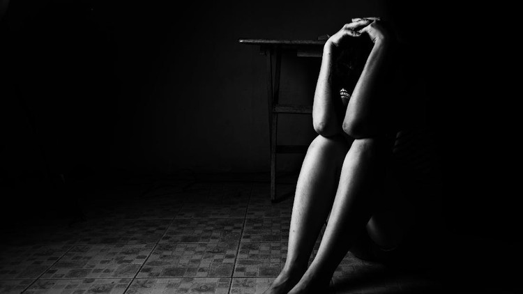 a woman sitting on ground with arm around lower head, sexual violence , sexual abuse, human trafficking concept with shadow edge in white tone