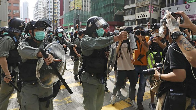 A riot police points the pepper spray to journalists as pro-democracy activists gather outside a shopping mall during the Labor Day in Hong Kong, Friday, May 1, 2020 amid an outbreak of the new coronavirus. May Day usually brings rallies and celebrations rallies marking international Labor Day. This year it's a bitter reminder of how much has been lost for the millions left idle or thrown out of work thanks to the coronavirus pandemic. (AP Photo/Kin Cheung)