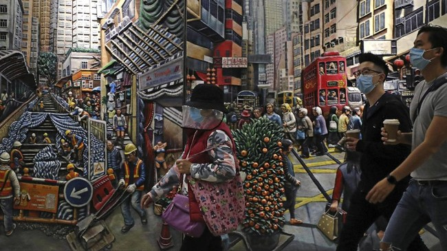 People wearing face masks to protect themselves from possibly contracting the coronavirus COVID-19 as they walk past a painting in Hong Kong, Saturday, April 25, 2020. (AP Photo/Kin Cheung)