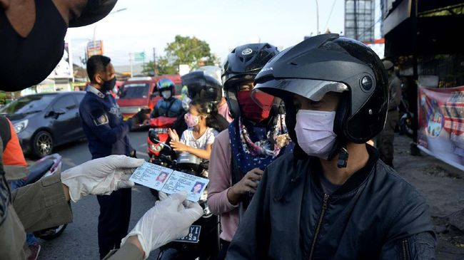Petugas gabungan memeriksa identitas pengendara motor saat penerapan Pembatasan Sosial Berskala Besar (PSBB) di perbatasan Makassar, Sulawesi Selatan, Jumat (1/5/2020). Pemeriksaan identitas tersebut untuk menertibkan setiap pengendara yang akan memasuki kota Makassar dalam rangka kepatuhan terkait aturan Pembatasan Sosial Berskala Besar (PSBB) yang diterapkan di Makassar. ANTARA FOTO/Abriawan Abhe/wsj.