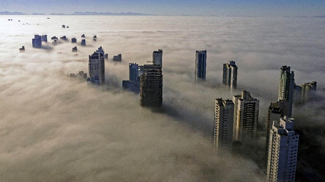 Fog covers skyscrapers in Curitiba on April 26, 2020. (Photo by DANIEL CASTELLANO / AFP)