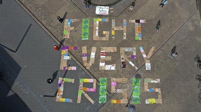 An aerial view shows demonstrators of the Fridays for Future environmental movement practicing social distancing as they stand next to placards arranged to form the words 'fight every crisis' in front of the city hall in Essen, western Germany, on April 24, 2020. - The climate movement Fridays for Future wants to demonstrate for more climate protection in many countries amid the Corona crisis. Because of the worldwide pandemic, the actions are taking place mainly on the Internet. (Photo by Ina FASSBENDER / AFP)