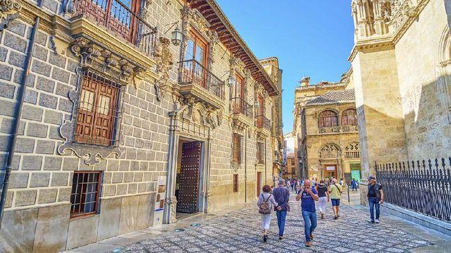Granada, Spain - September 25, 2019: Tourists walk in Calle Oficios (La Lonja square), lined with historic buildings of Capilla Real (Royal Chapel) and Palacio de la Madraza (Madrasah school)