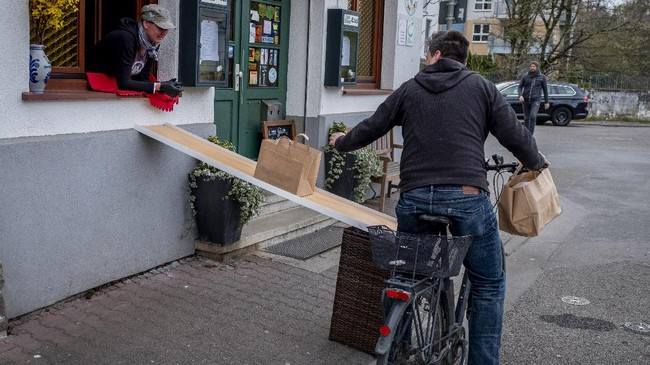 FILE - In this April 3, 2020, file photo, a man on a bike picks up food to go in front of the apple cider restaurant 'Zum Lahmen Esel' in Frankfurt, Germany. Cycling activists from Germany to Peru are trying to use the moment to get more bike lanes, or widen existing ones, even if it is just a temporary measure to make space for commuters on two wheels. (AP Photo/Michael Probst, File)