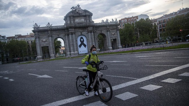 In this photo taken on Saturday, April 25, 2020, a woman rides Madrid's electric bike hire service BiciMAD in front of a Puerta de Alcala square with a black ribbon for the victims of COVID-19 as the lockdown to combat the spread of coronavirus continues in downtown Madrid, Spain. As countries seek to get economies back on track after the outbreak, bicycle use is being encouraged as a way to avoid any unsafe crowding on trains and buses. (AP Photo/Manu Fernandez)