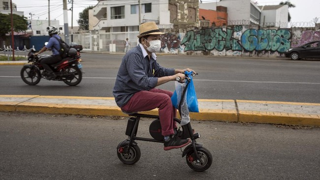 FILE - In this April 11, 2020, file photo, a man wearing a protective face mask as a precaution against the new coronavirus, rides on an electric bike in Lima, Peru. Cycling activists from Germany to Peru are trying to use the moment to get more bike lanes, or widen existing ones, even if it is just a temporary measure to make space for commuters on two wheels. (AP Photo/Rodrigo Abd, File)